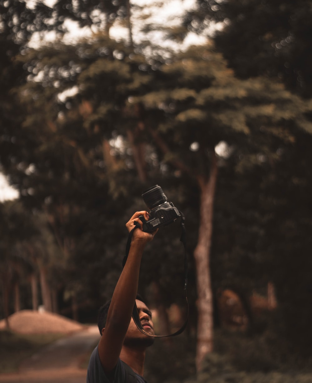 person holding black smartphone taking photo of trees during daytime