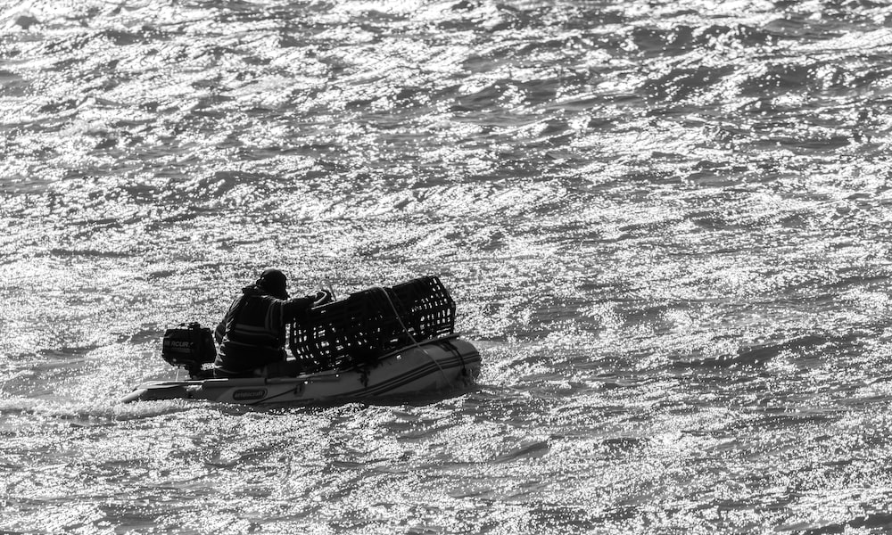 grayscale photo of a boat on the sea