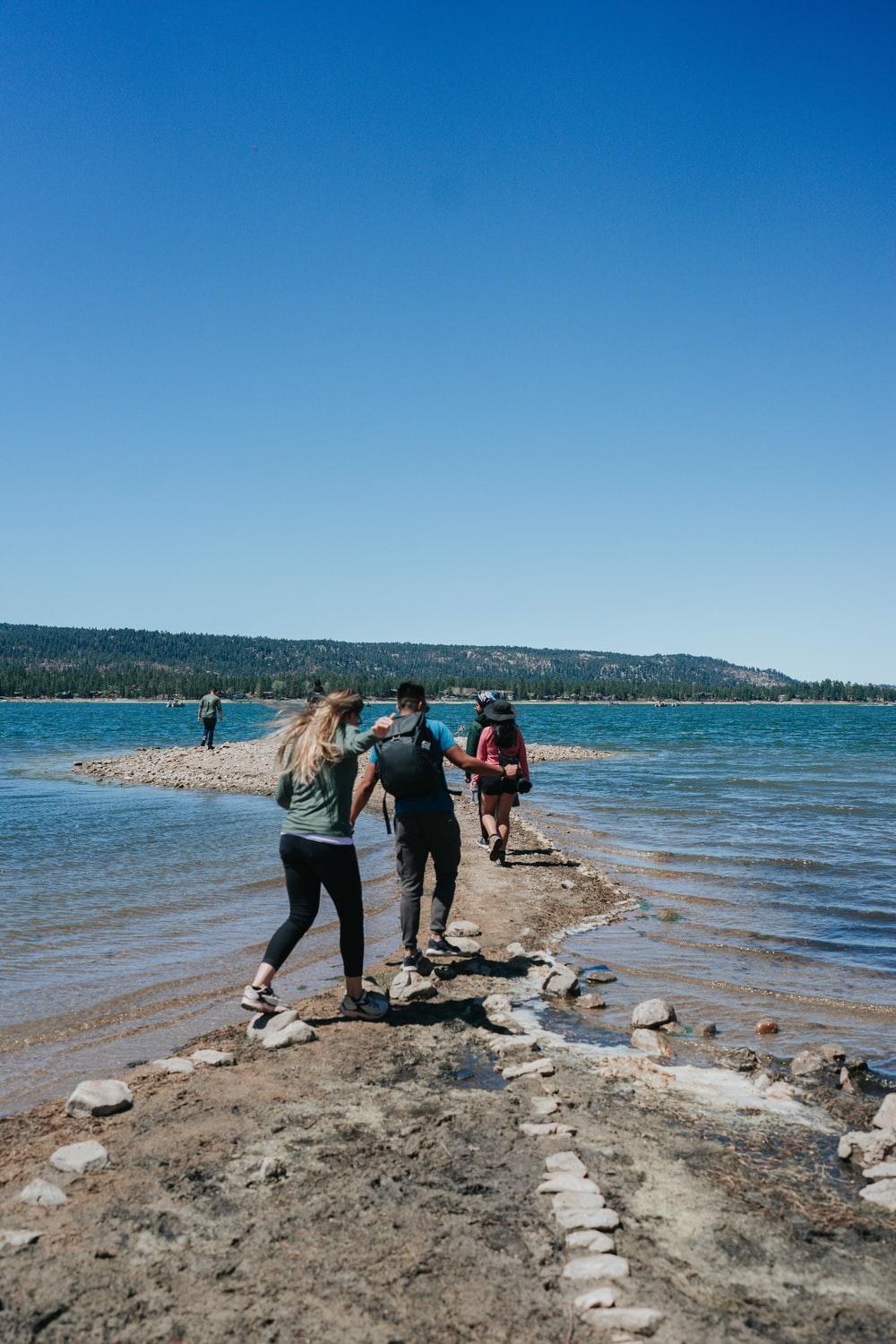 people standing on brown rock near body of water during daytime