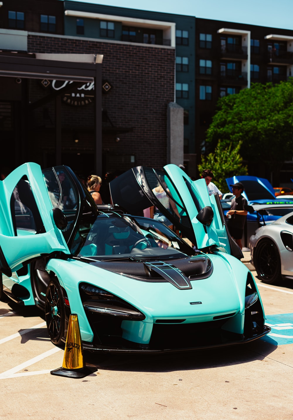 blue and black sports car parked beside blue car during daytime