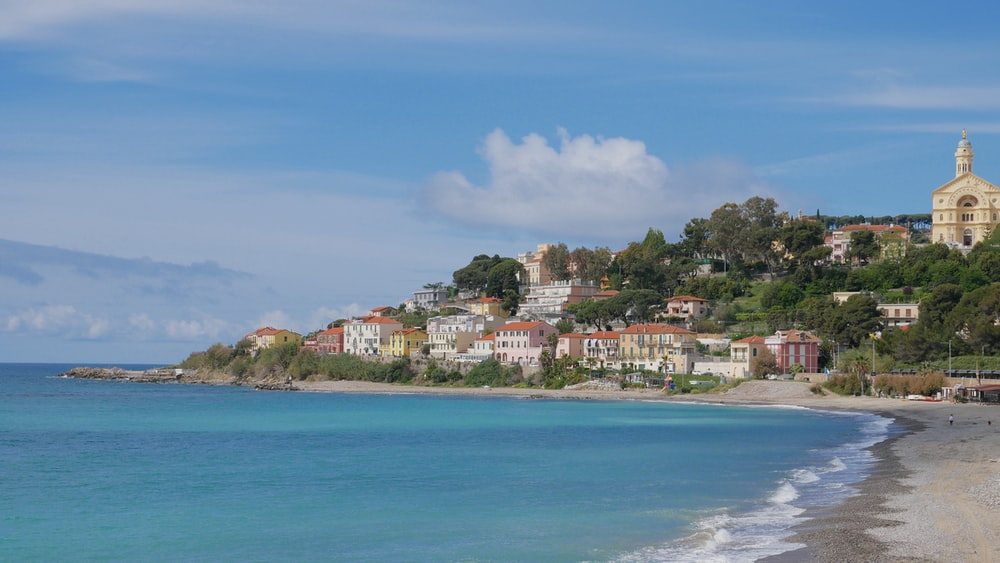 houses near sea under blue sky during daytime