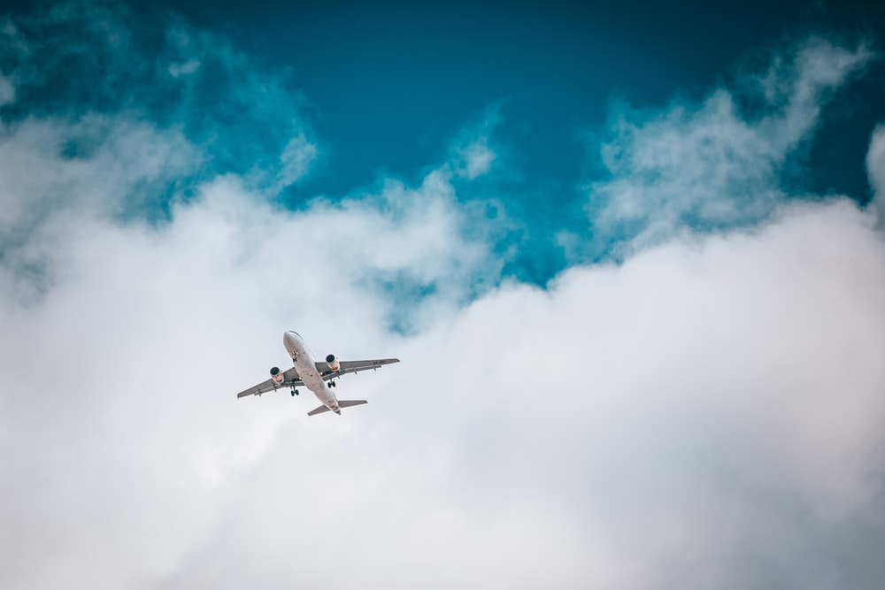white airplane under blue sky and white clouds during daytime
