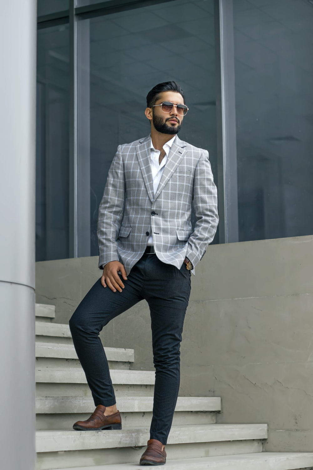 man in blue and white pinstripe dress shirt and blue denim jeans standing beside white wall