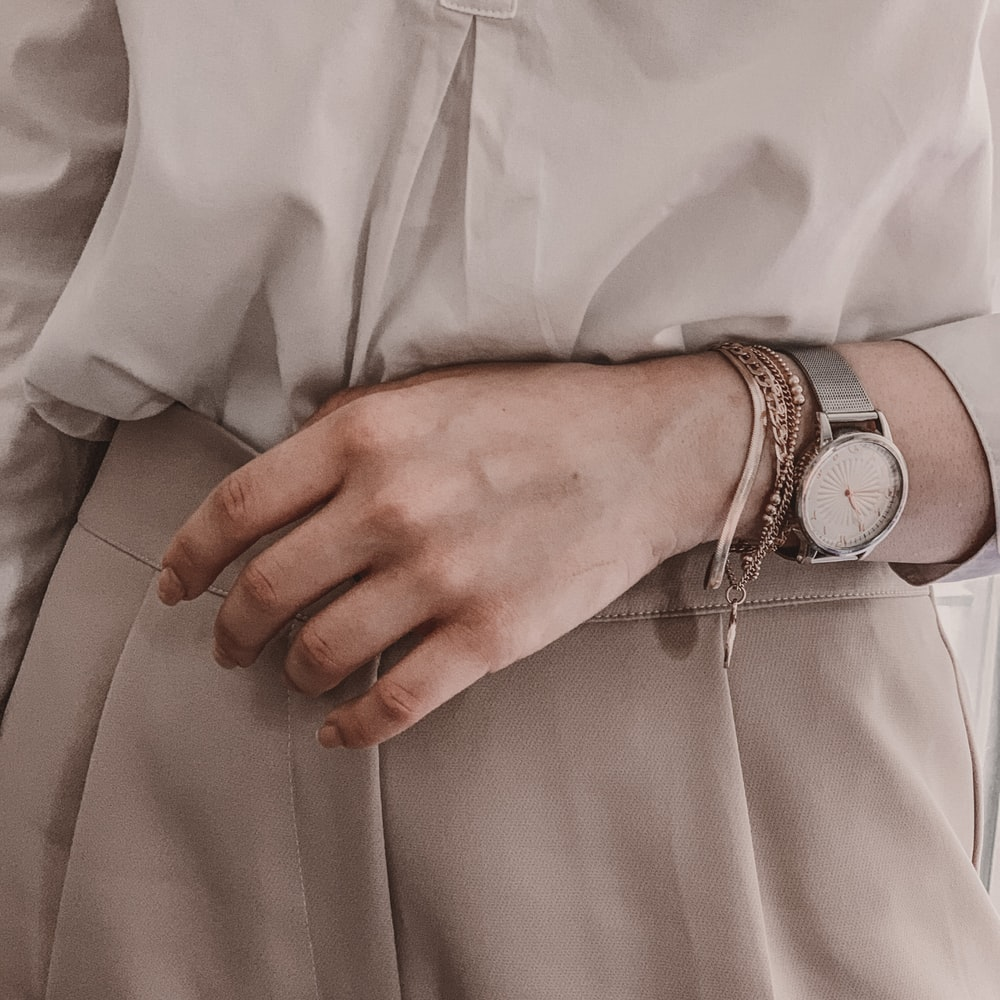 person in white dress shirt wearing silver link bracelet round analog watch