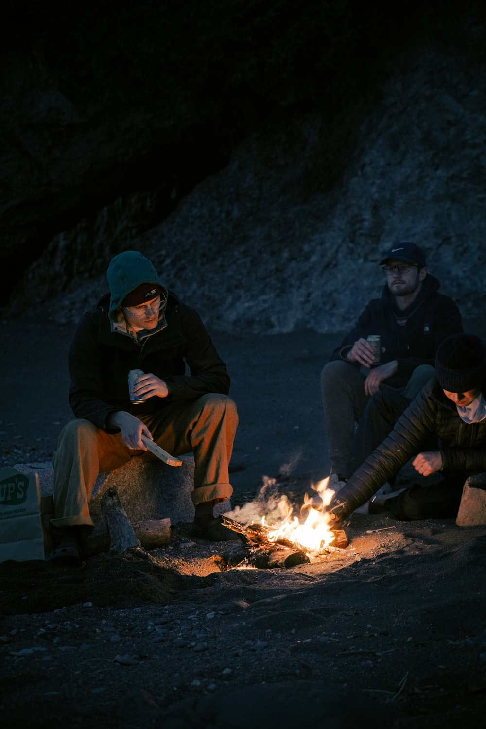 man and woman sitting on brown log near bonfire during daytime