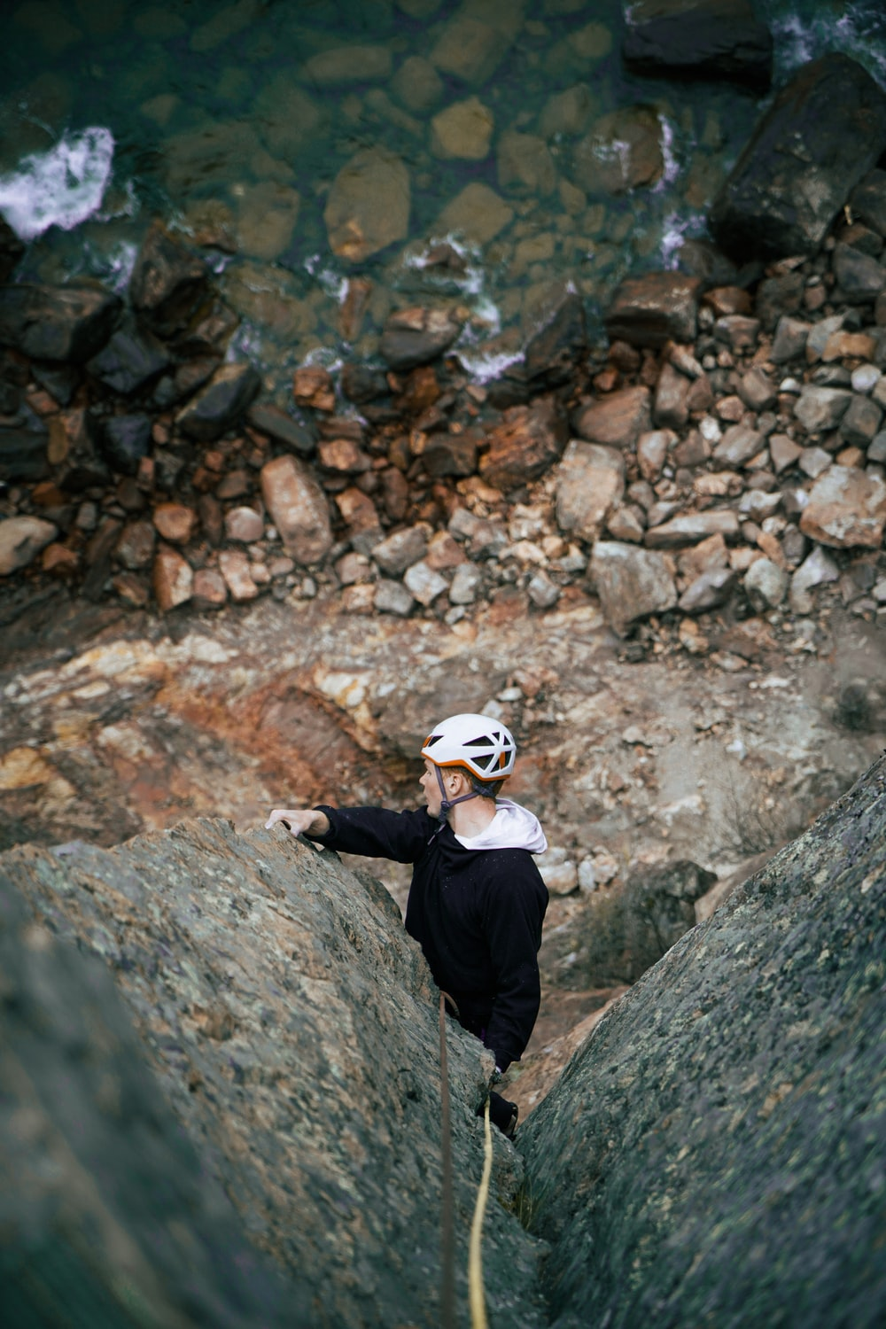man in black jacket and white cap standing on rocky ground