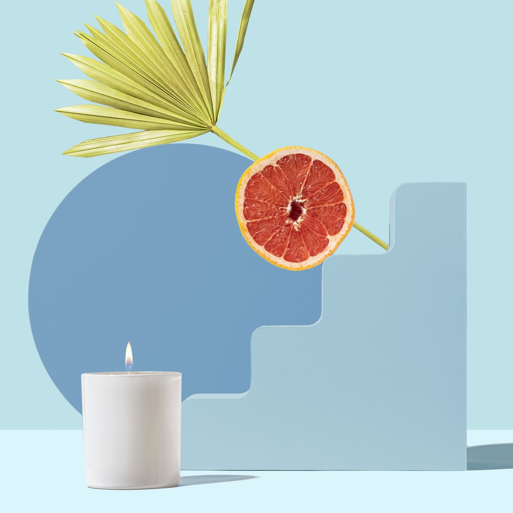 orange fruit beside white pillar candle
