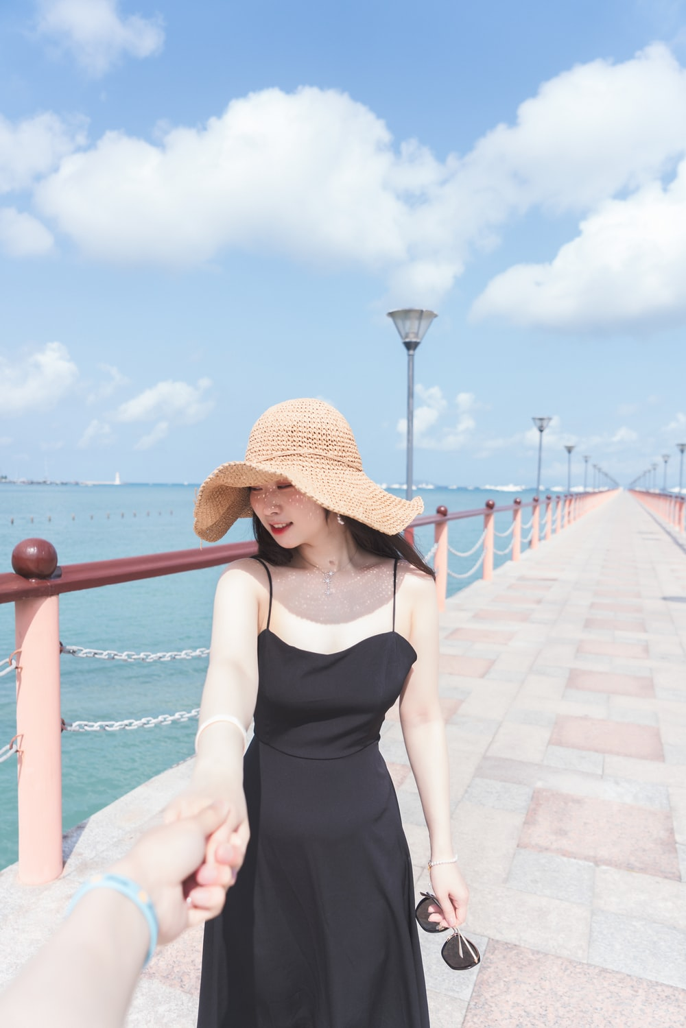 woman in black tank top wearing brown sun hat standing beside red metal railings during daytime