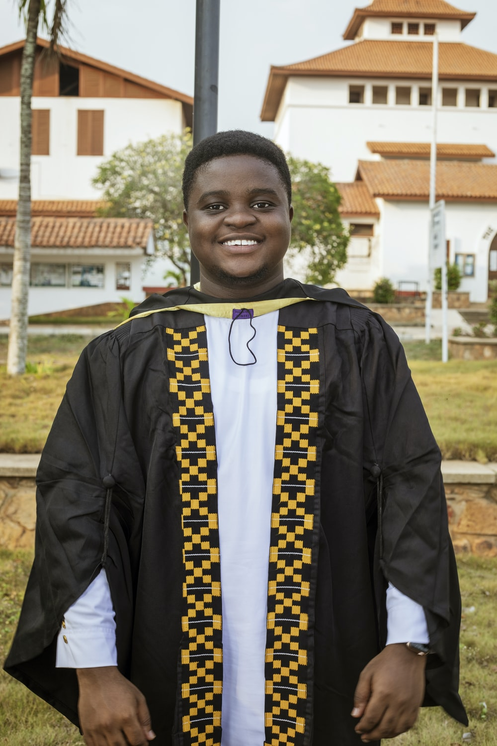 boy in black and yellow academic dress