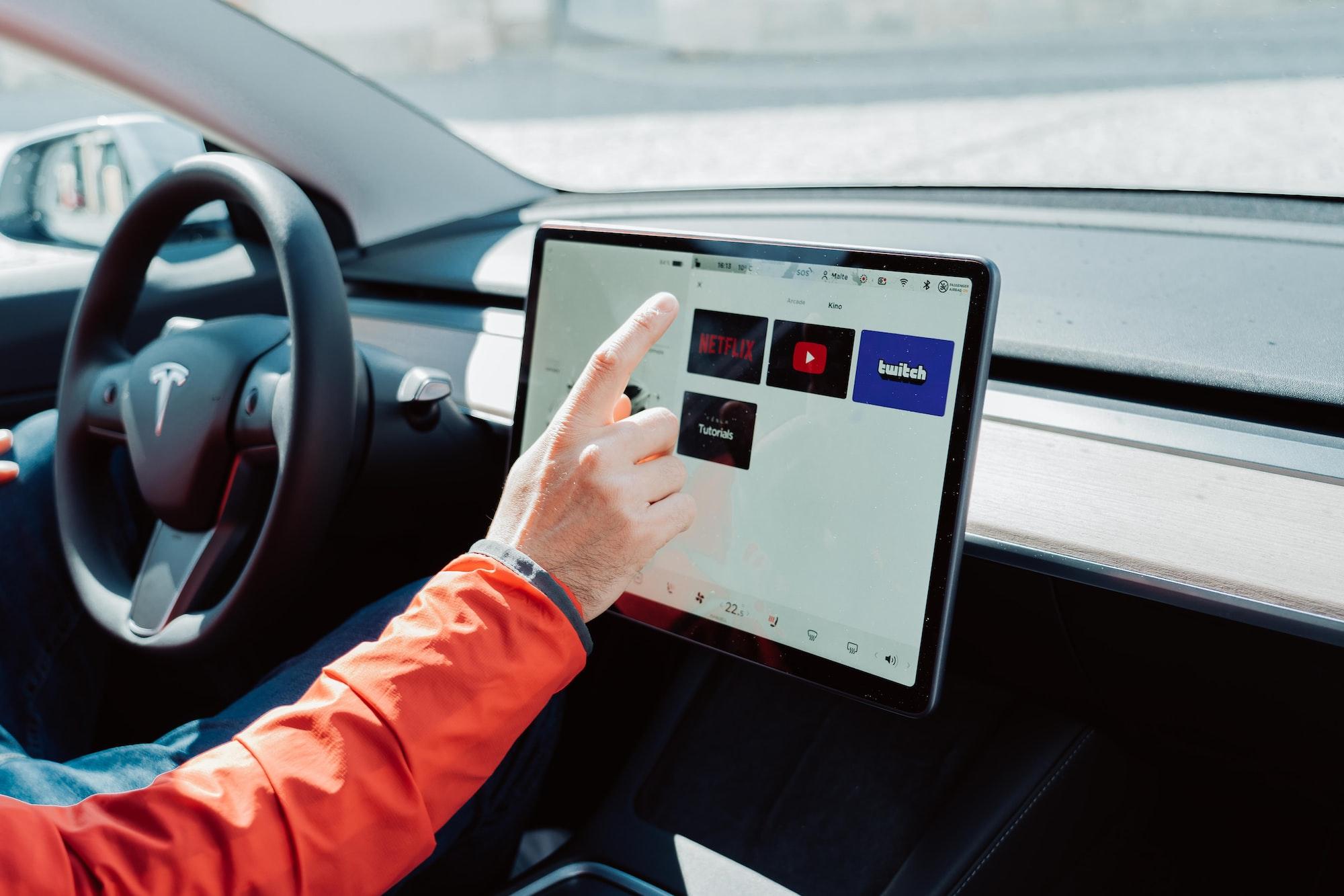 Man in orange jacket is sitting in Tesla and using Tesla app