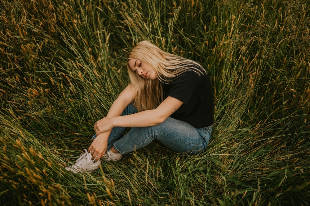 woman in black t-shirt and blue denim jeans sitting on grass field