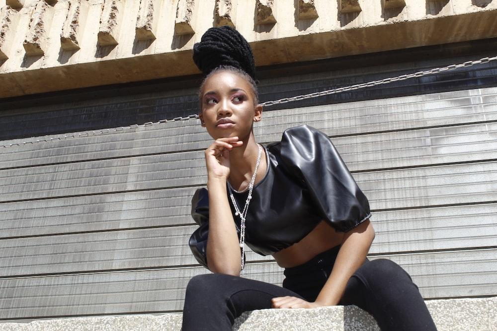 woman in black shirt sitting on gray concrete bench