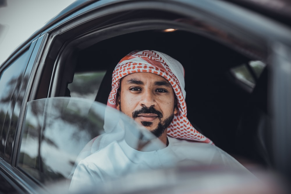 man in white long sleeve shirt wearing red and white hijab inside car