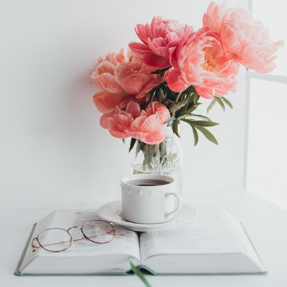 pink flowers on white ceramic mug on white ceramic saucer