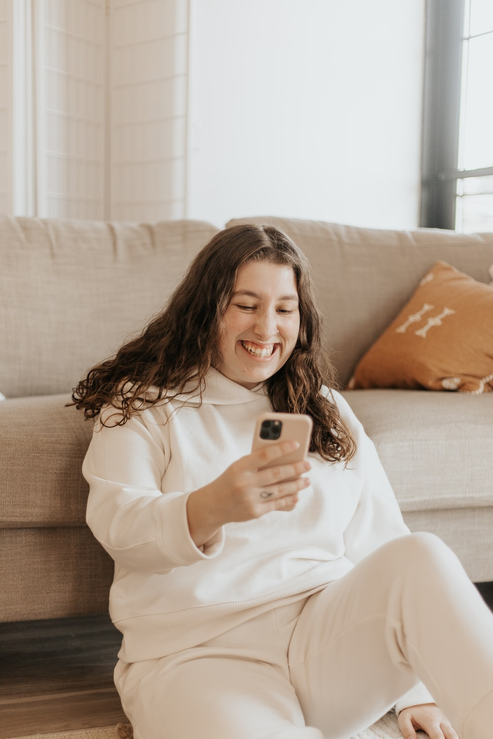 woman in white long sleeve shirt holding iphone