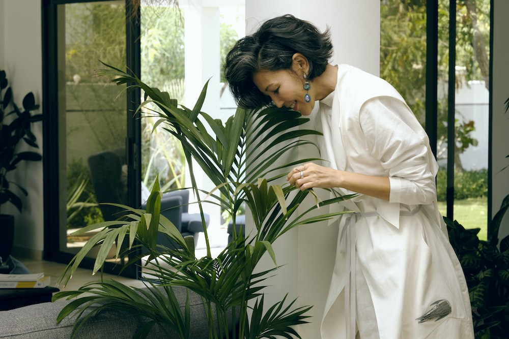 woman in white robe holding green plant