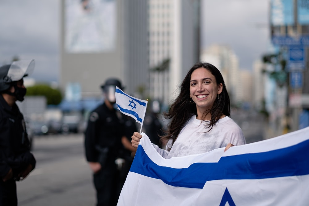 woman in white and blue long sleeve shirt holding blue and white flag