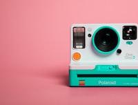 teal and white polaroid camera