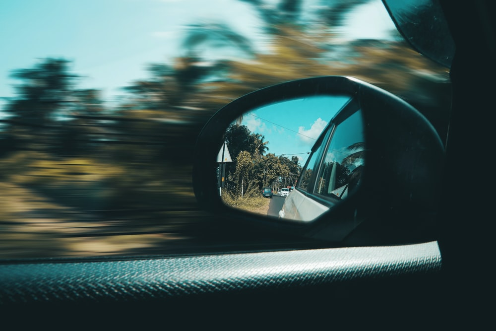car side mirror with a reflection of sun