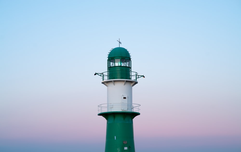 green and white lighthouse under white sky during daytime