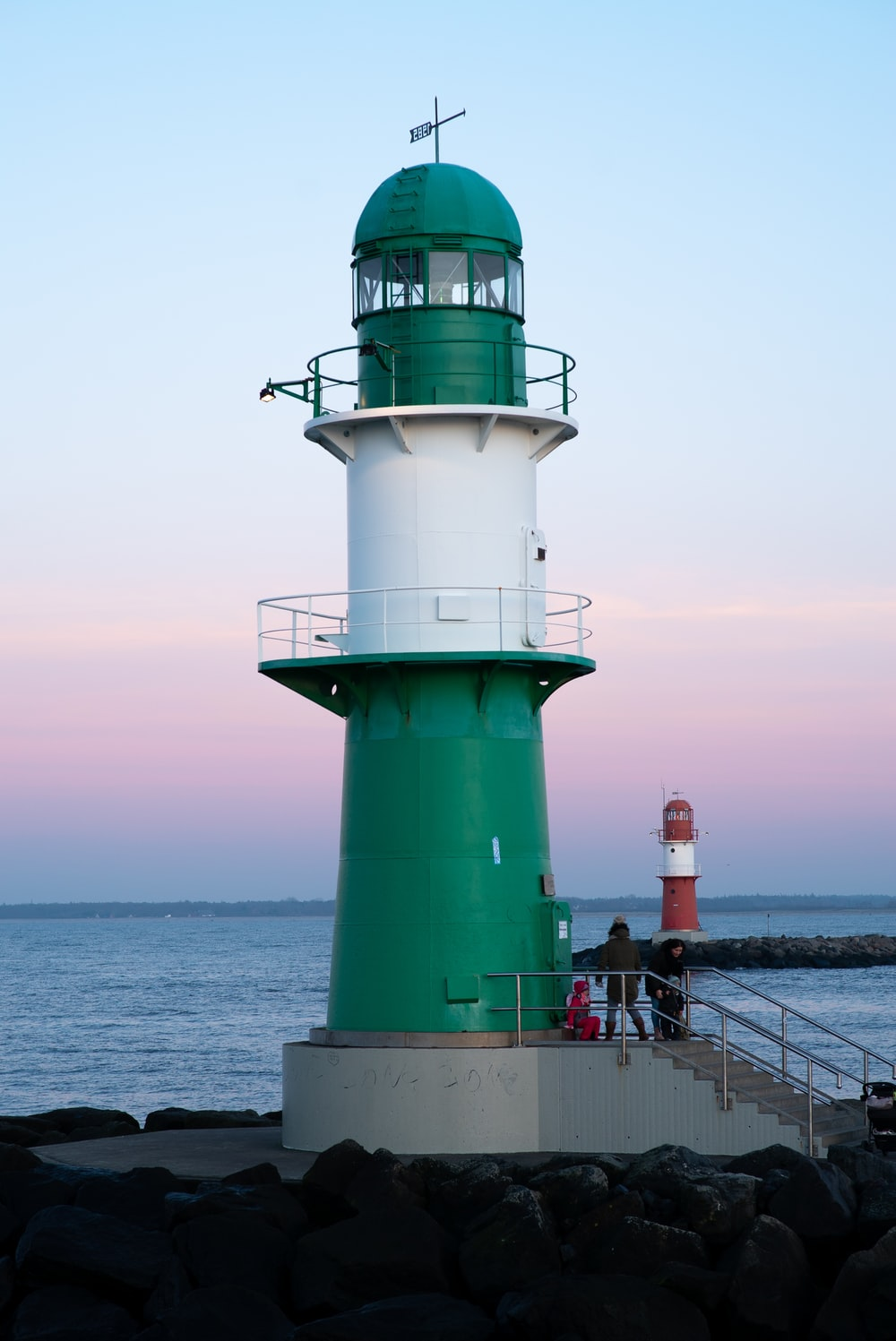 white and green lighthouse on sea during daytime