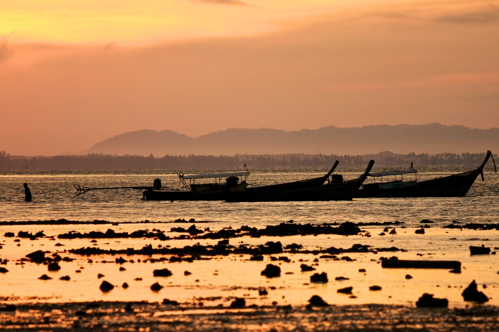 white boat on sea during sunset