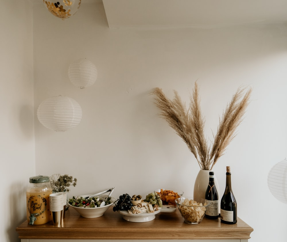 brown wheat on white ceramic bowl beside bottles on brown wooden table