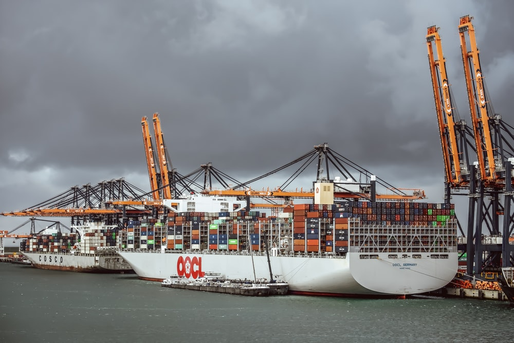 white and blue cargo ship on sea under gray clouds