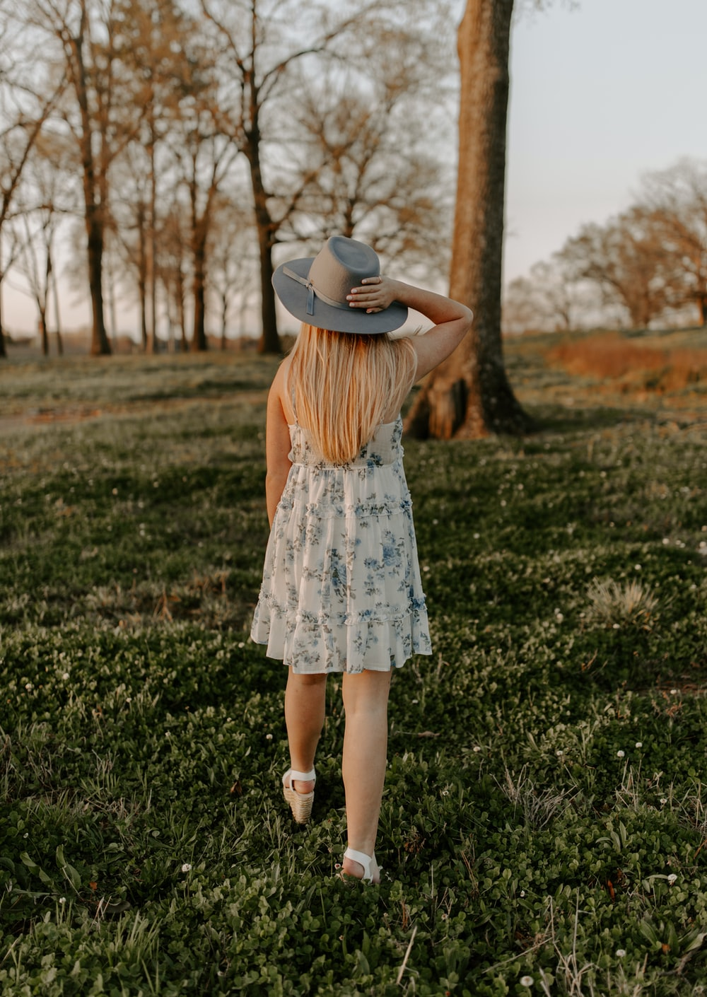 woman in white and blue floral dress wearing brown hat standing on green grass field during
