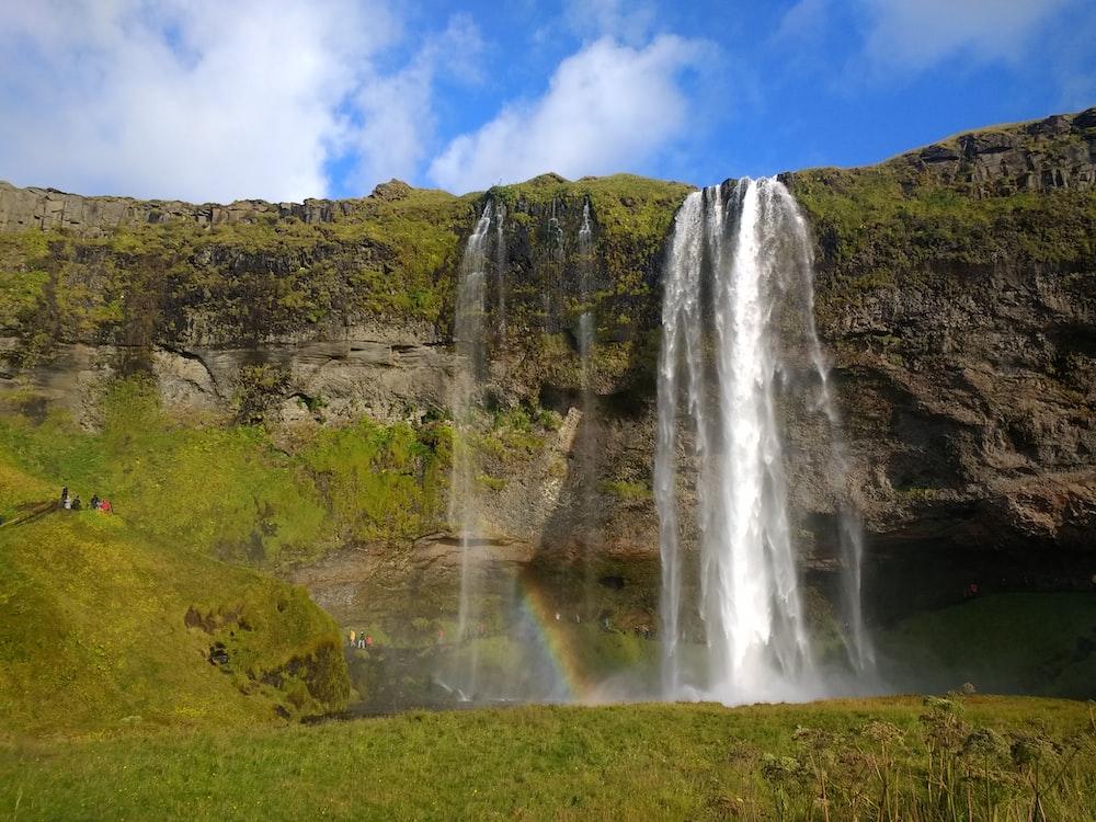 waterfalls on green grass field under blue sky during daytime