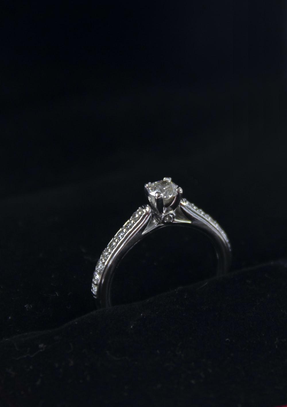 silver diamond ring on black textile