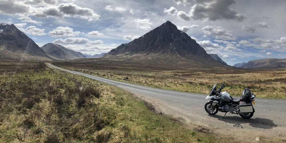 white and black motorcycle on road near mountain under white clouds during daytime