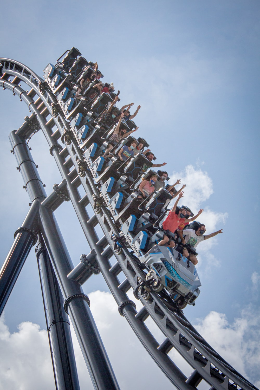 people riding on roller coaster during daytime