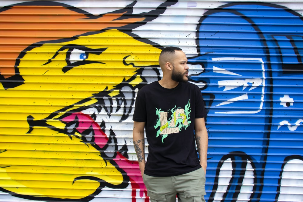 man in black crew neck t-shirt standing beside yellow and blue surfboard