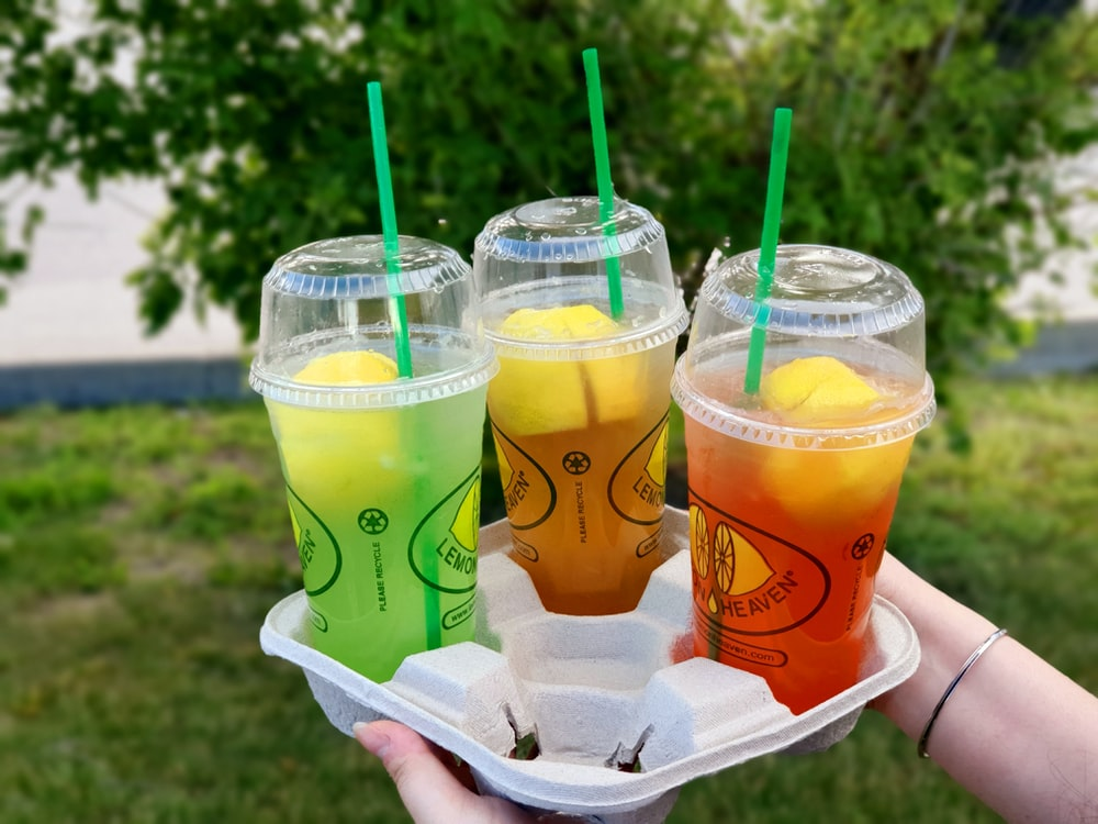 two clear plastic disposable cups with green straw