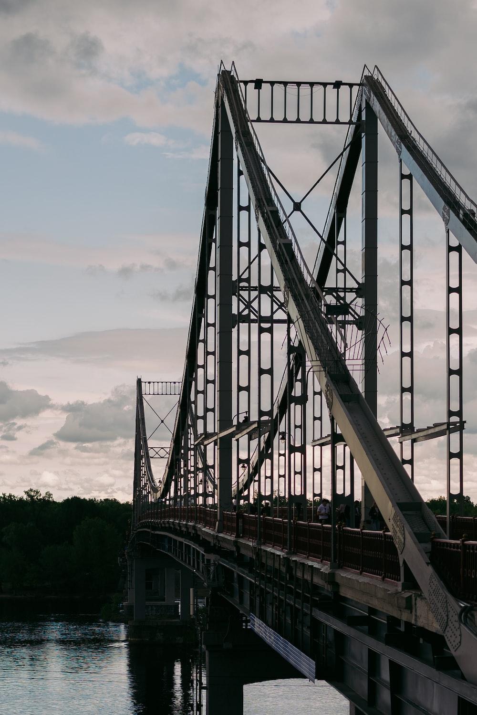 gray metal bridge over green trees during daytime