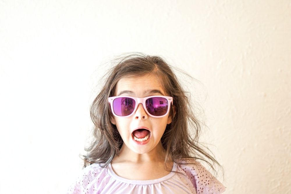girl in white and purple floral crew neck shirt wearing blue framed sunglasses
