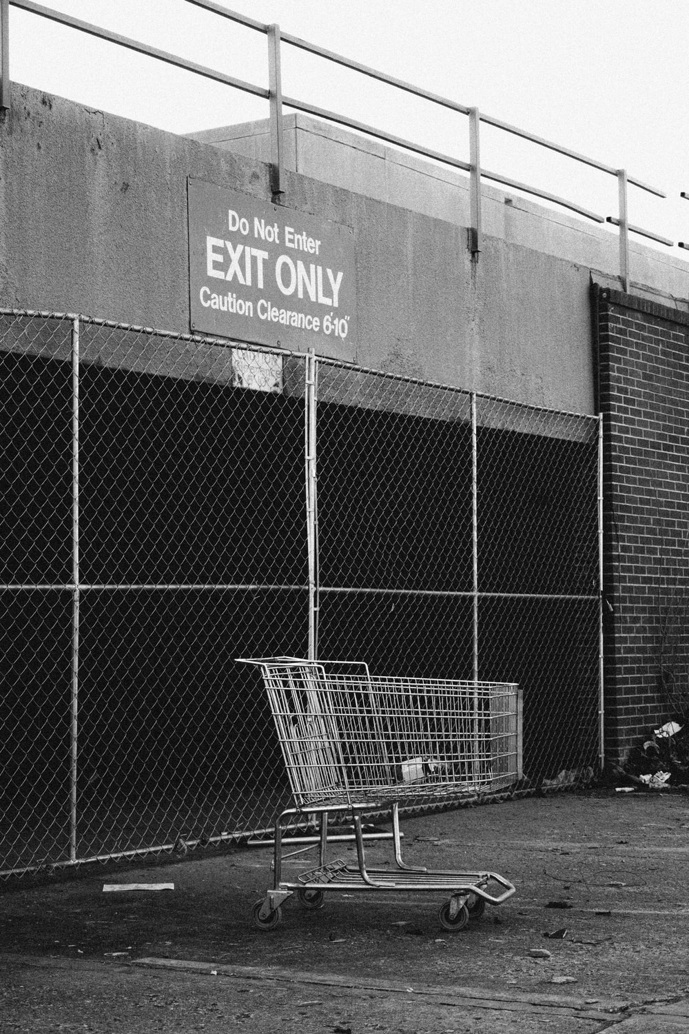 grayscale photo of shopping cart near building