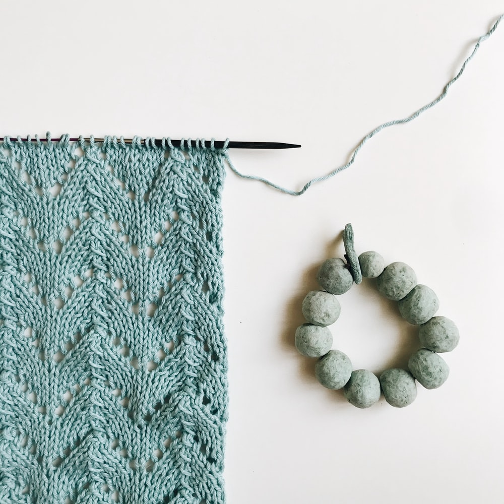 green knit textile beside white and gray stones