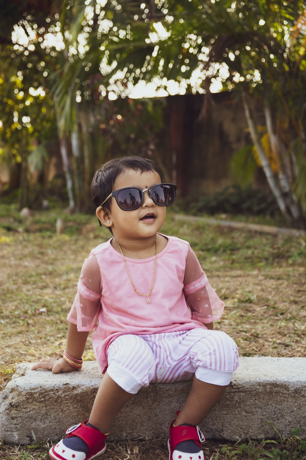 girl in pink shirt and white pants sitting on ground
