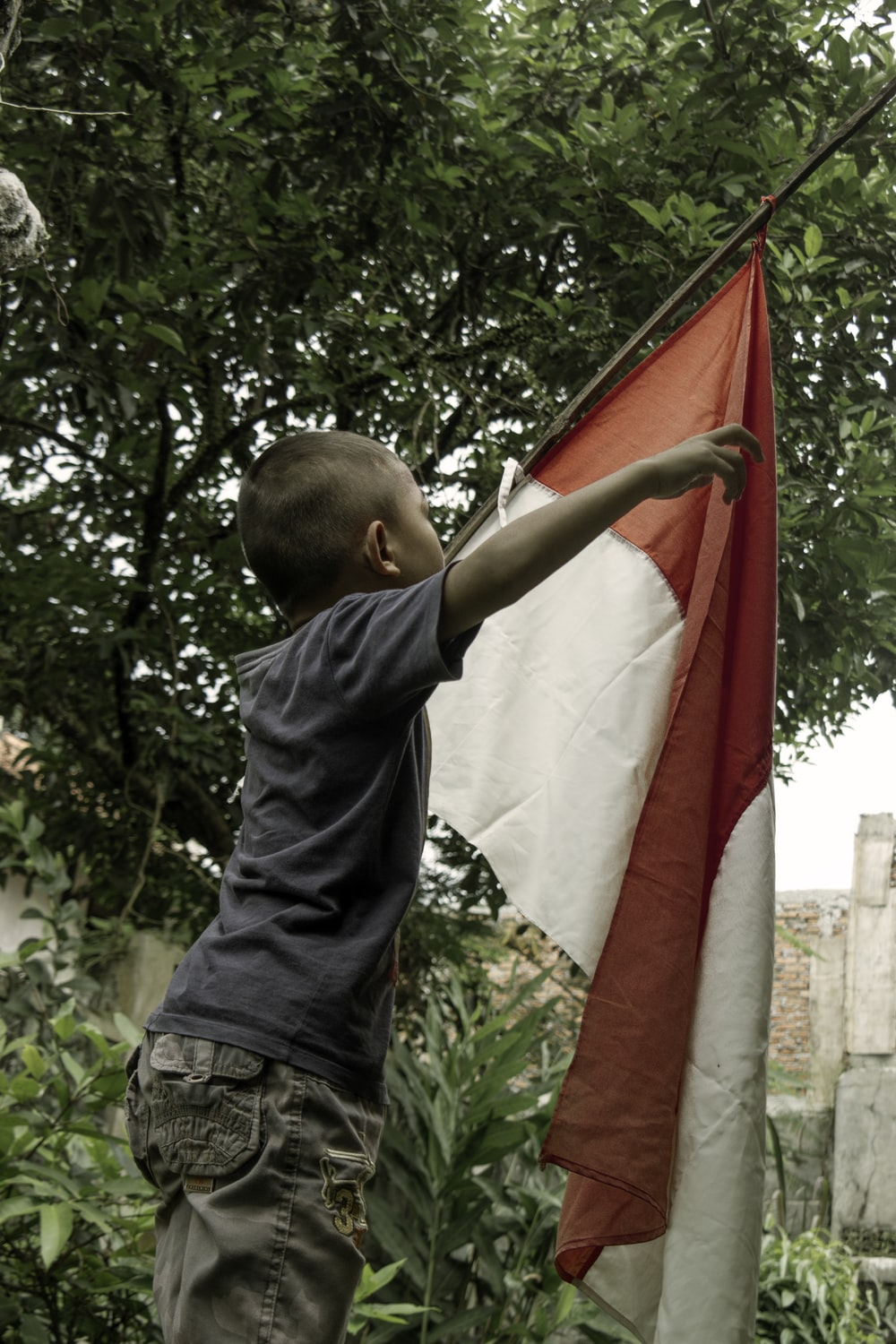 boy in black shirt holding red and white flag