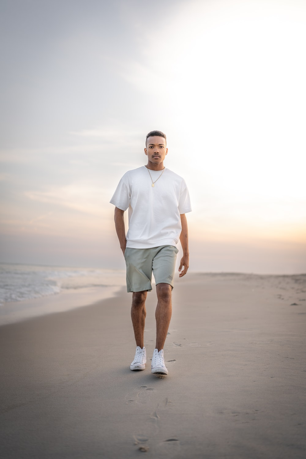 man in white crew neck t-shirt and green shorts standing on beach during daytime