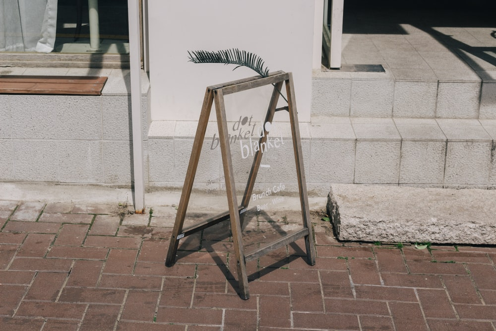 brown wooden folding ladder leaning on white concrete wall