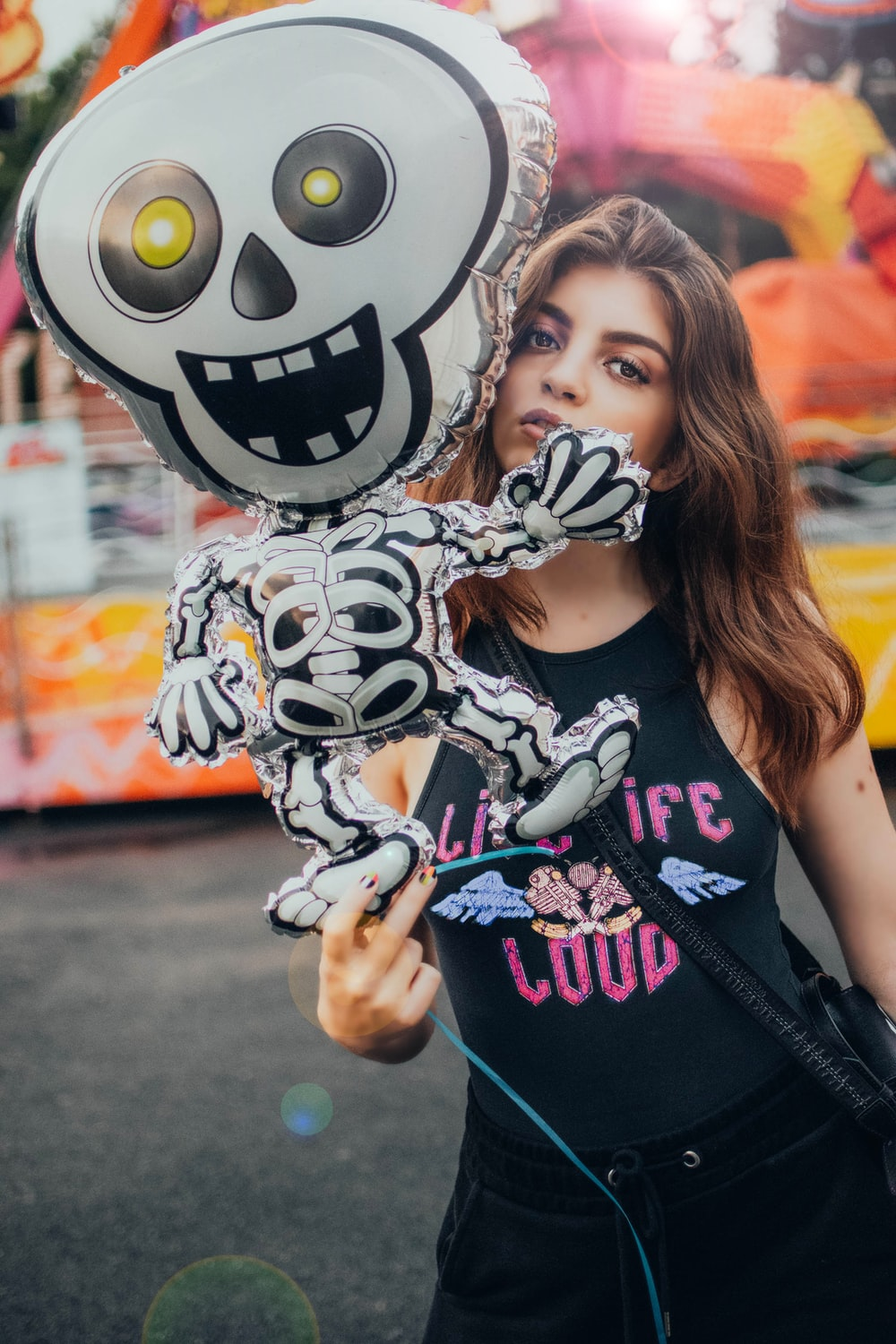 woman in black tank top holding white and black skull print balloon