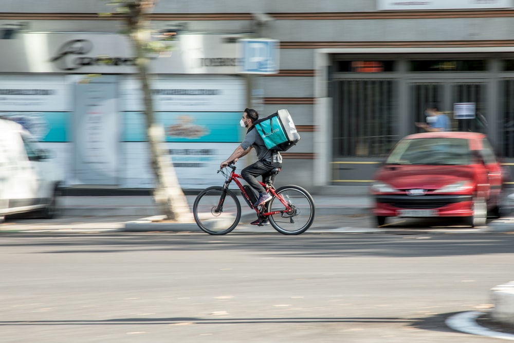 man in blue shirt riding bicycle on road during daytime