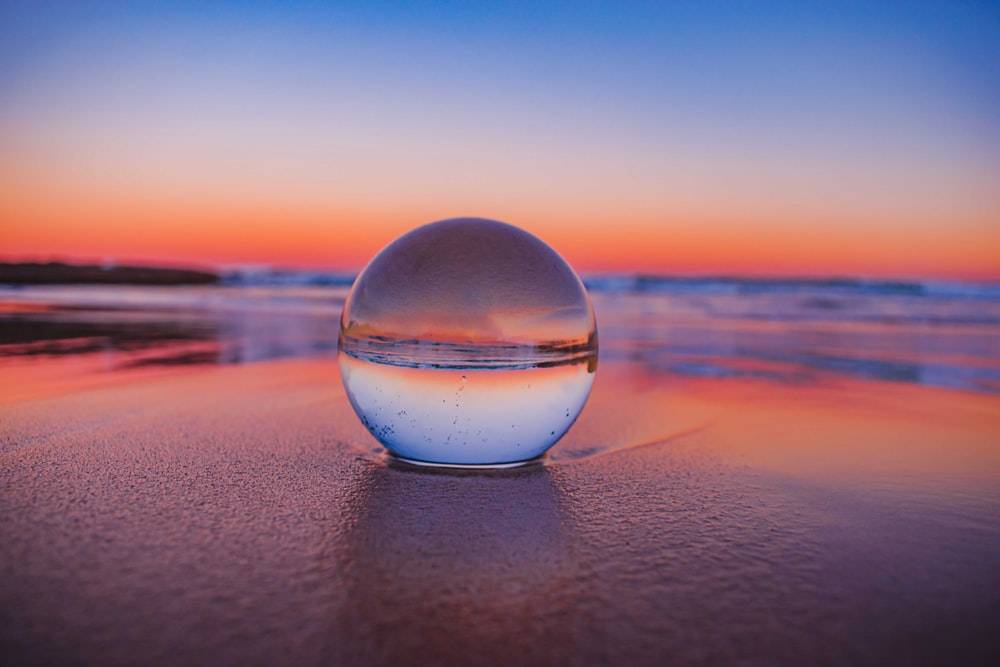 clear glass ball on gray sand during sunset