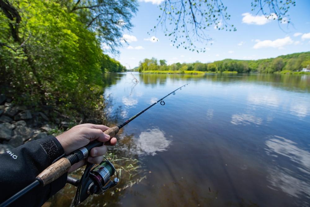 person holding black fishing rod near lake during daytime