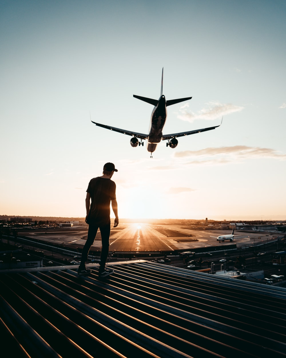 man standing on top of building looking at airplane in the sky during sunset