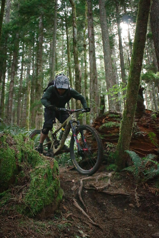man in black jacket riding black mountain bike in forest during daytime