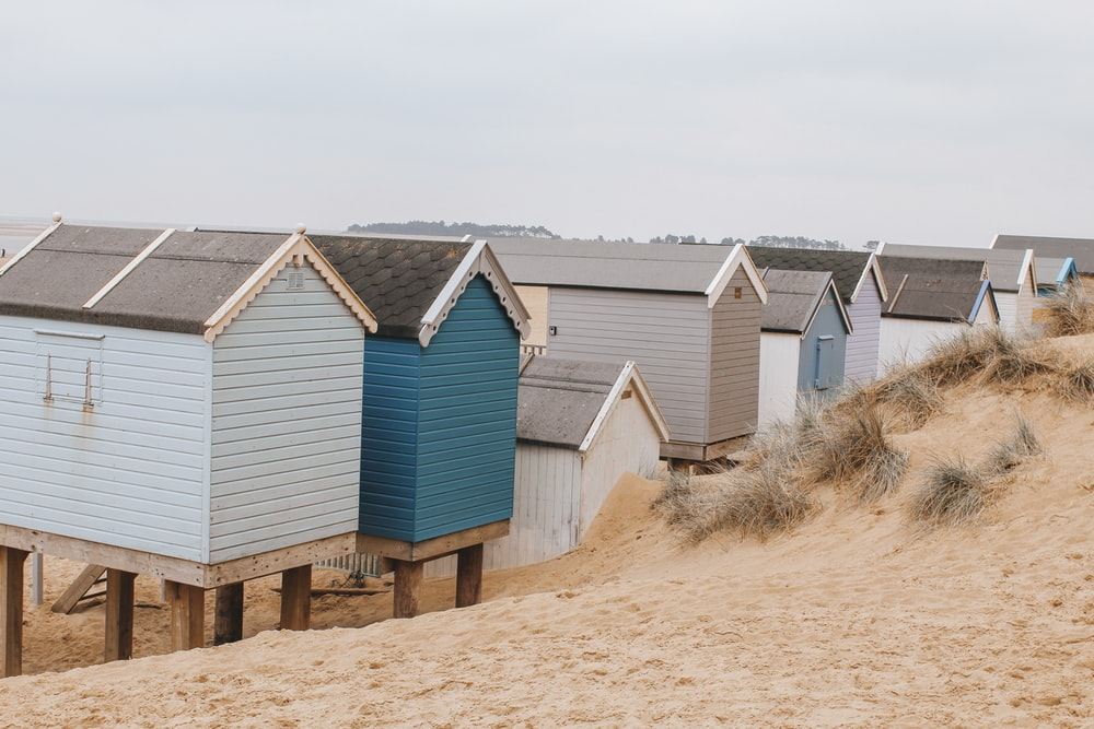 blue and white wooden house on brown sand during daytime